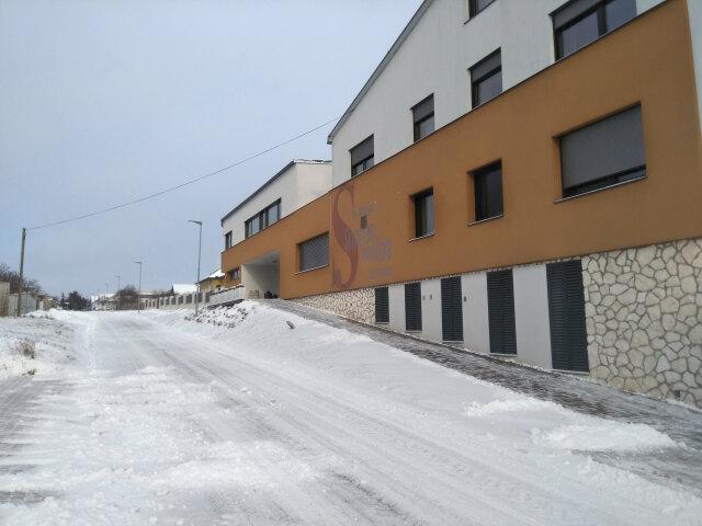 Blick auf das Weingut und einen Teil der Goldbersgstraße. Es liegen etwa 10 cm Schnee, der aber schon von Straße und Gehsteigen geräumt und auf Haufen zusammengeschoben wurde.