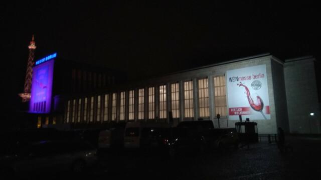 Halle der Messe Berlin bei Nacht. Ein beleuchtetes Plakat der Weinmesse an der Fassade, im Hintergrund der ebenfalls beleuchtete Funkturm
